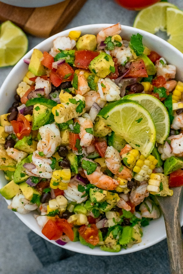 White bowl filled with salad that contains shrimp, avocados, tomatoes, onion, and various vegetables. All tossed with a cilantro lime dressing.