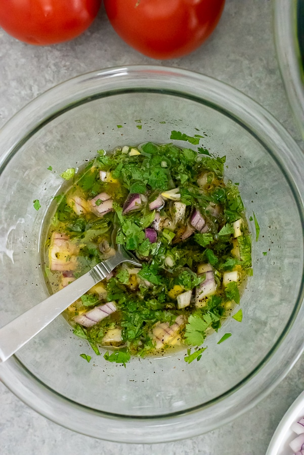 Clear mixing bowl containing cilantro lime dressing.
