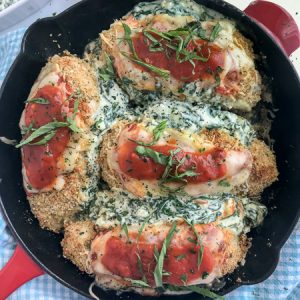 Spinach and Cream Cheese Stuffed Chicken Parmesan - this baked chicken recipe is the bomb when it comes to flavor! The chicken is stuffed with spinach and cream cheese and coated with a crispy breadcrumb coating. Tender and juicy on the inside, crispy on the outside, and flavorful throughout. Best part? All you need is one pan. #chickenparmesan #chicken #onepan #dinner #stuffedchicken | www.withpeanutbutterontop.com