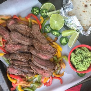 The Best and Easiest Garlic Lime Steak Fajitas -  these steak fajitas are easier to make than you think and absolutely delicious! Tender marinated flat iron steak served with sautéed bell peppers, onions, and a creamy Cilantro Lime Avocado Mash. #steak #dinner #easy #steakfajitas #fajitas #mexican #onepan | www.withpeanutbutterontop.com