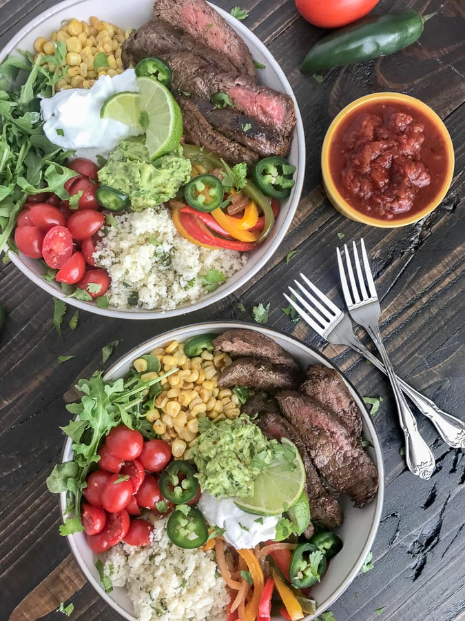 Steak Fajita Bowls with Garlic Lime Cauliflower Rice - these fajita bowls will complete your Taco Tuesday cravings! The steak is marinated in a garlic lime sauce and is super tender, as well as flavorful. #bowls #healthy #steakfajitas #fajitas | www.withpeanutbutterontop.com