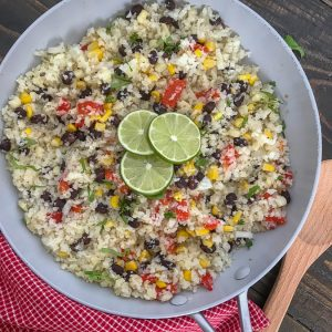 Cilantro Lime Black Bean and Corn Cauliflower Rice - an incredibly easy and flavorful side dish that is packed full of veggies and can be on your plate in 15 minutes or less! 115 calories per serving! #healthy #cauliflowerrice #glutenfree #vegan #healthy   https://withpeanutbutterontop.com