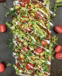 Loaded Skinny Taco Flatbread Pizza - a healthier, lower-carb version of our favorite pizza! Loaded with toppings, easy and quick to make! #pizza #tacos #tacopizza #tacotuesday   https://withpeanutbutterontop.com
