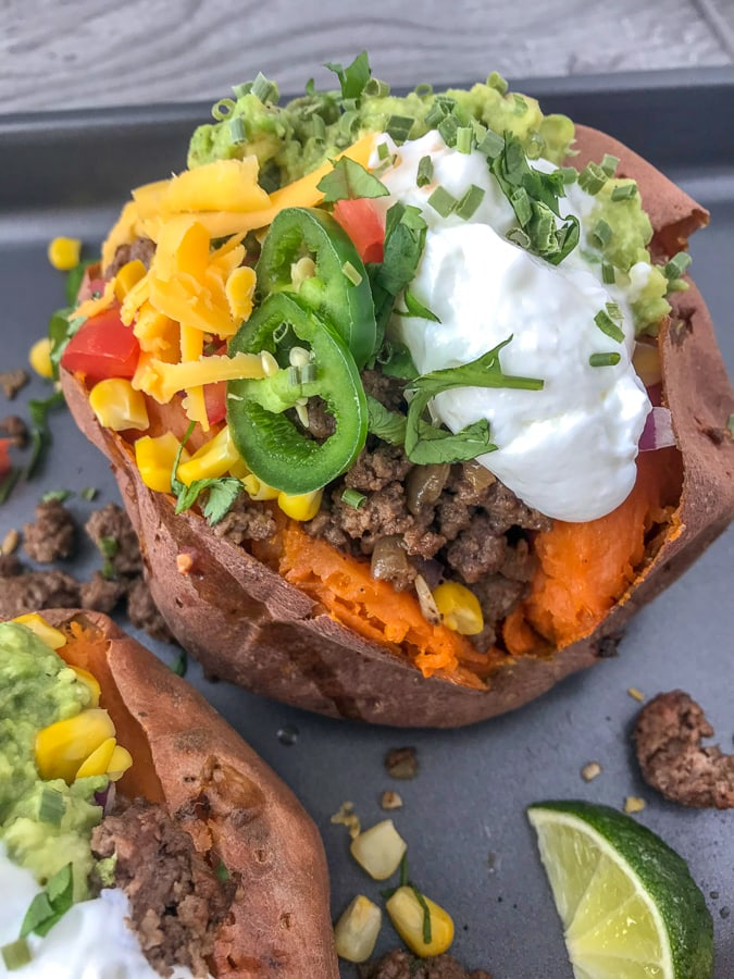 Taco Stuffed Sweet Potatoes - a simple and easy healthy spin on #TacoTuesday that you and your family are going to absolutely love! Full of flavor and perfect for those taco cravings! #taco #tacos #healthy #stuffedsweetpotatoes #tacostuffed   https://withpeanutbutterontop.com