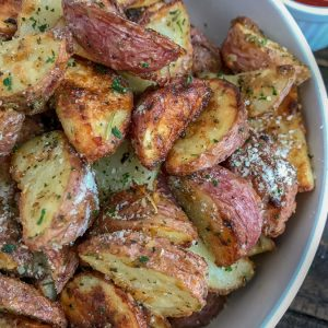 Super Crispy Garlic Parmesan Potato Bites - this is the perfect side dish to your dinner tonight! Easy to make, ready in 30-35 minutes, and sure to be a hit at your table! Crispy on the outside and light and fluffy on the inside like potatoes should be! #sidedish #crispypotatoes #ovenroastedpotatoes #baked | https://withpeanutbutterontop.com