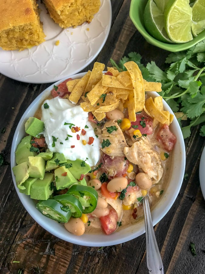Easy One Pot White Chicken Chili - lightened up! This chili is filled with chicken breast, beans, corn, tomatoes, and that great Tex Mex flavor! Simple to make and all done in one pot! #easy #easydinners #healthy #soups   https://withpeanutbutterontop.com
