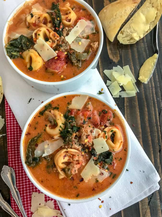 One Pot Sausage Tortellini Tomato Soup - a super delicious and easy recipe that is filled with turkey sausage, cheese tortellini, kale, and herbs in a delicious tomato base! Hearty, filling, and yummy! #soup #healthysoup #sausagetortellinisoup | https://withpeanutbutterontop.com