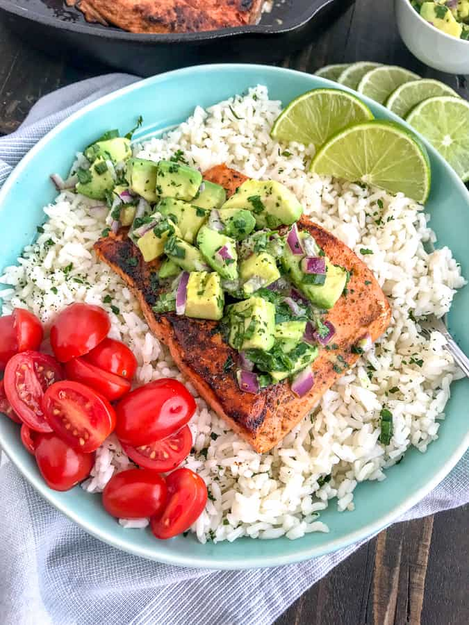 Super simple, quick and healthy recipe! Perfectly seasoned and pan seared salmon over a bed of cilantro lime rice and garnished with a creamy avocado salsa that is bursting full of flavor! #cajunsalmon #salmon #searedsalmon #salmonbowl | https://withpeanutbutterontop.com