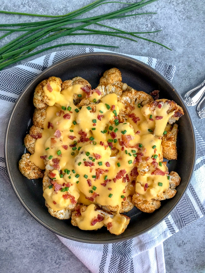 Fork tender cauliflower seasoned and roasted to perfection in a creamy cheddar cheese sauce. A lighter, healthier version of macaroni and cheese that is full of so much flavor - you'll forget about the pasta! #roastedcauliflower #cauliflower #cauliflowerandcheese #appetizer | https://withpeanutbutterontop.com