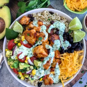 Tender, juicy chicken, Avocado Corn Salsa, and black beans served over brown rice and drizzled in Creamy Cilantro Lime Sauce. So much flavor you will forget that you're eating healthy! #tacotuesday #tacos #tacobowl #healthy   https://withpeanutbutterontop.com