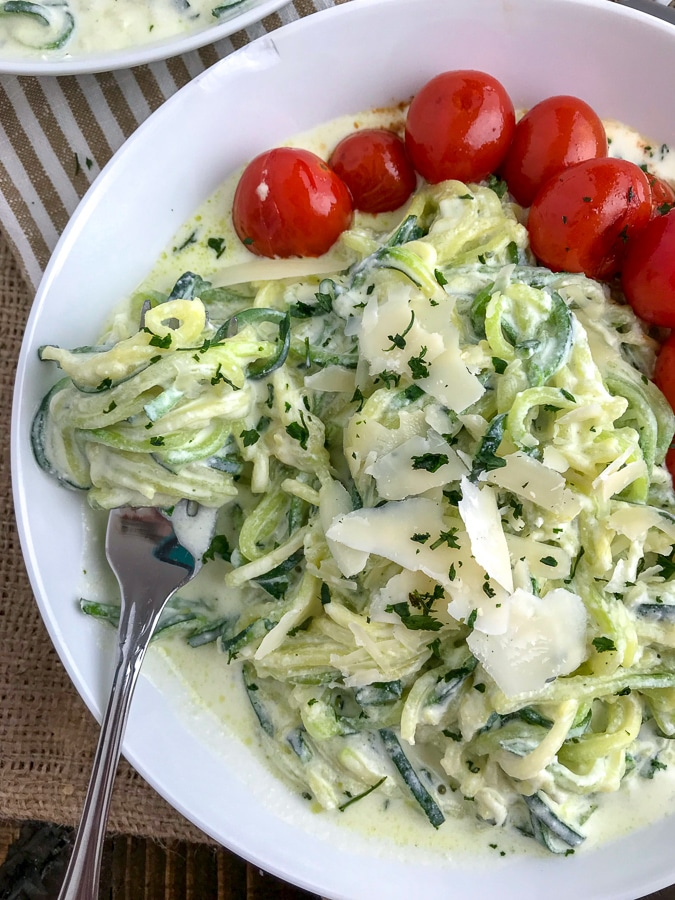 A light, fresh and easy dinner that will curb any creamy pasta craving! Cooked, tender zucchini noodles tossed in a creamy, garlic parmesan ricotta sauce and served with a side of blistered cherry tomatoes. The perfect healthy dinner option! #zoodles #parmesanzoodles | https://withpeanutbutterontop.com