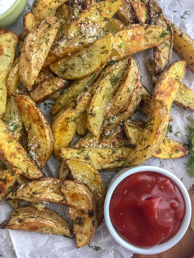 Calling all dill pickle lovers! These potato wedges are crispy on the outside, while being tender and flaky on the inside, with a hint of delicious dill pickle flavoring! The perfect appetizer or side dish to grilled chicken or burgers! #dillpickle #potatowedges #appetizer | https://withpeanutbutterontop.com