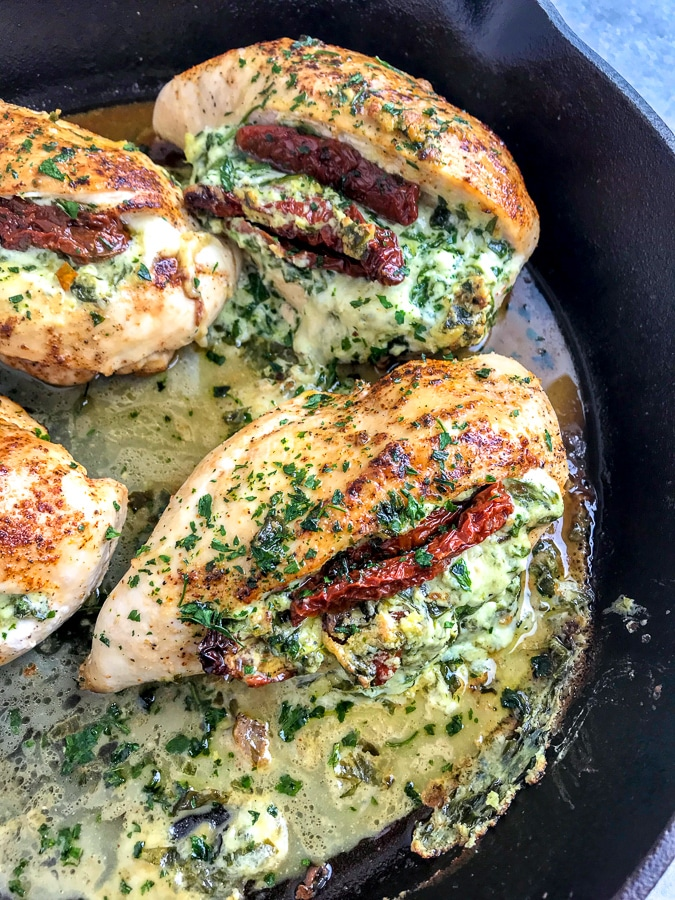 Creamy and cheesy spinach and sun-dried tomato stuffed chicken breast that is undeniably delicious! You will be savoring each bite! A wonderful spin on stuffed chicken that will delight your family at the dinner table! #stuffedchicken #chicken #creamyspinach | https://withpeanutbutterontop.com