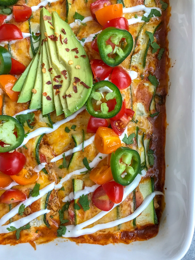 """Creamy, shredded chicken stuffed into zucchini """"rolls"""" and then baked in enchilada sauce and cheddar and monetary jack cheese. Very easy to make, low-carb, keto-friendly, and full of amazing flavors! #chickenenchiladas #lowcarb #keto #enchiladas   https://withpeanutbutterontop.com"""