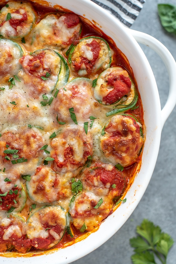 Baking dish filled with zucchini lasagna roll ups. Garnished with cheese and fresh seasonings. A great low-carb, gluten-free and healthy option to traditional lasagna.