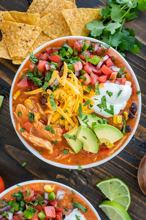 Bowl filled with soup and garnished with avocado, greek yogurt, cheddar cheese and pico de gallo.