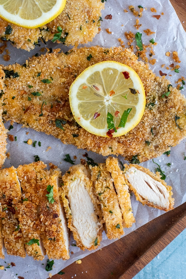 Platter with baked chicken breasts garnished with lemon slices.