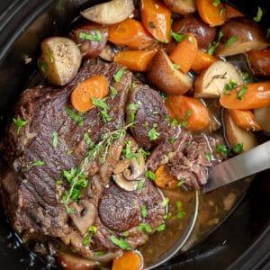 Crock pot filled with pot roast, potatoes, carrots, and mushrooms.