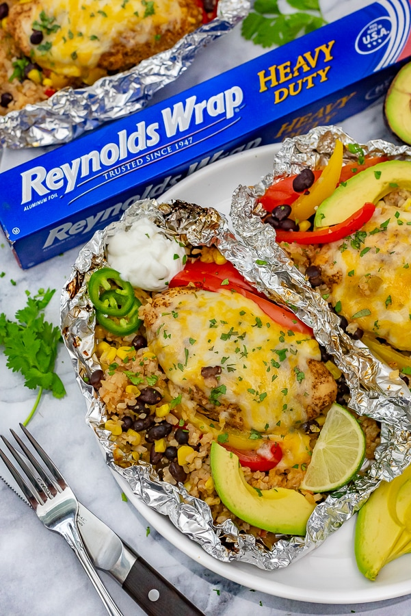 White plate with two grilled foil packets filled with veggies and chicken.