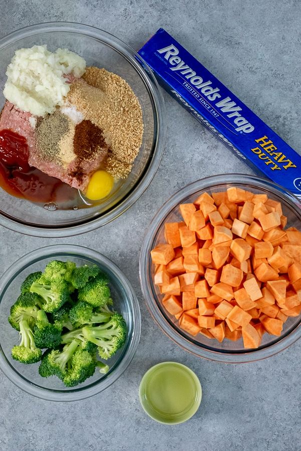 Three mixing bowls filled with ingredients to make turkey meatloaf with a side of broccoli and sweet potato chunks.