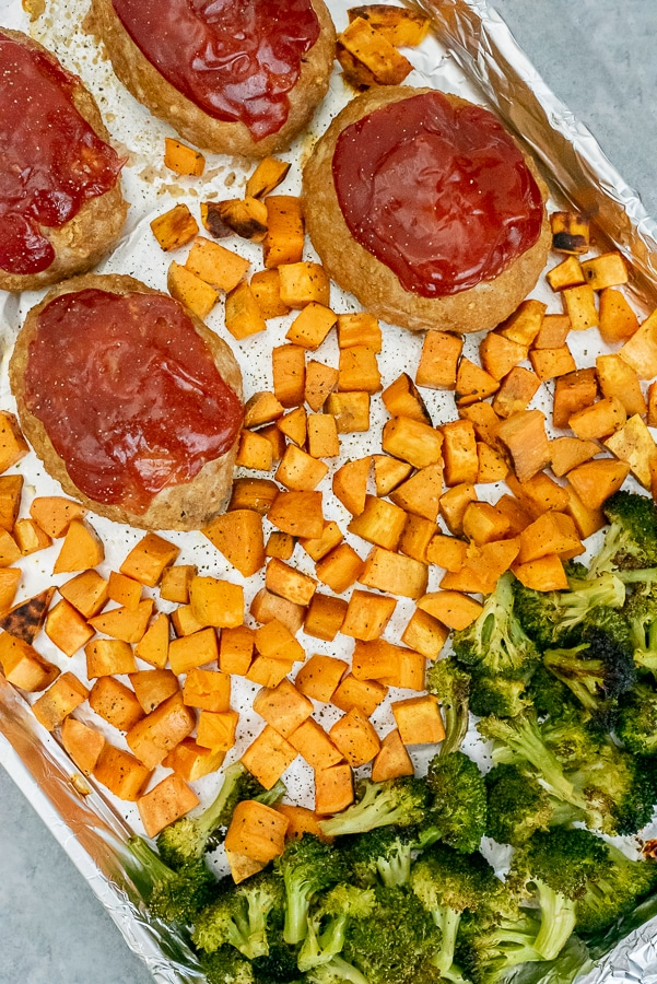 Sheet pan covered in aluminum foil containing mini turkey meatloaves, sweet potato chunks, and broccoli.