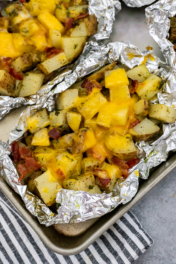 Sheet pan containing foil packets with cubed potatoes garnished with bacon, cheddar cheese, plain greek yogurt, and chives.
