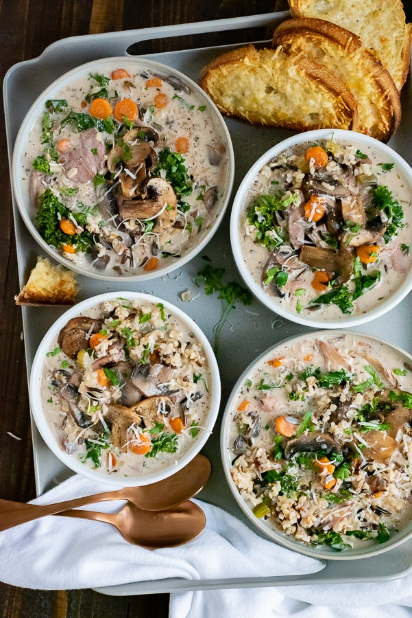 White bowls filled with a chicken and rice style soup, garnished with cheese bread.
