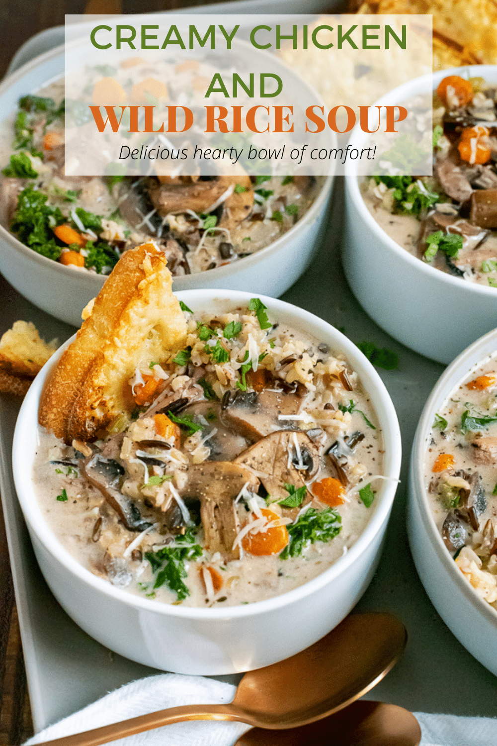 White bowls filled with creamy chicken and wild rice soup, garnished with cheese bread.