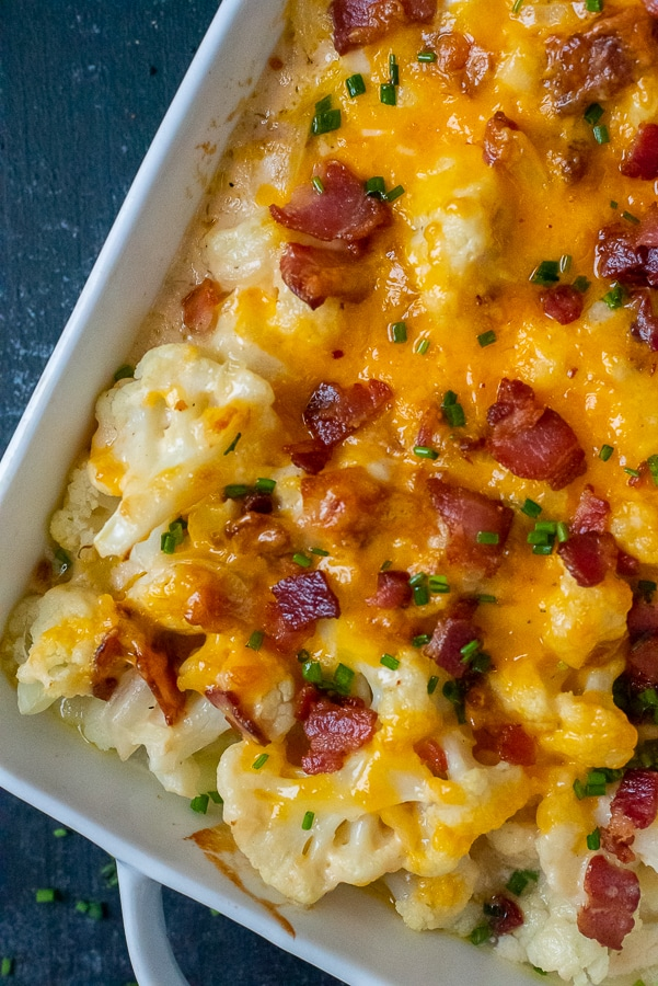 Casserole dish filled with creamy cauliflower topped with cheddar cheese, bacon, and chives.