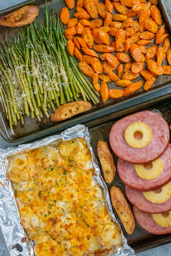 Two sheet pans filled with easter dishes: carrots, asparagus, scalloped potatoes, and ham.