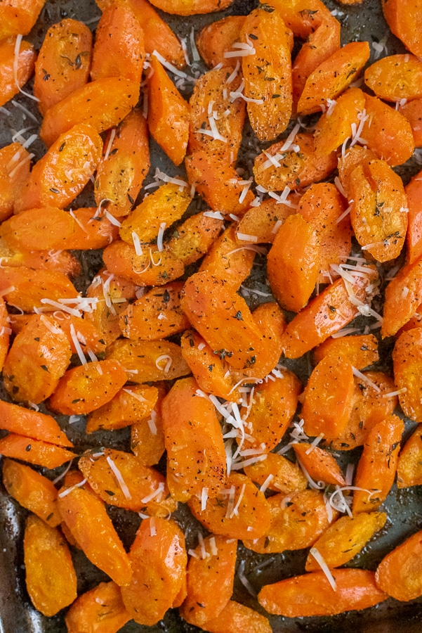 Sheet pan filled with sliced carrots garnished with thyme and parmesan cheese.