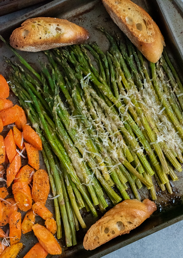 Sheet pan of asparagus garnished with freshly grated parmesan cheese.