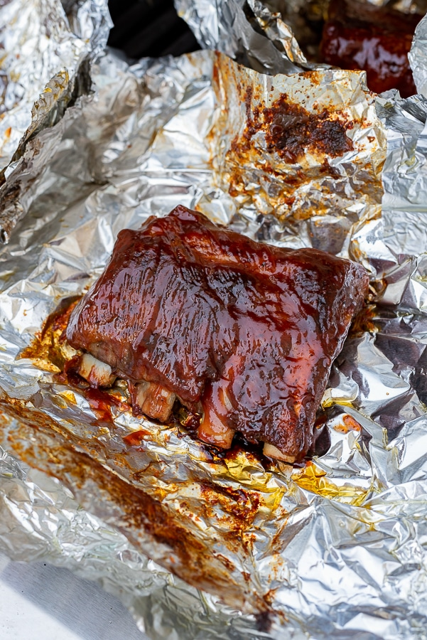 Ribs on the grill with foil underneath.