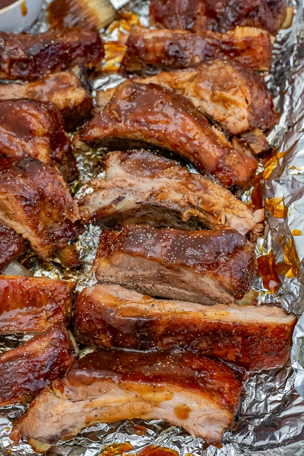 Sheet pan with bbq ribs and extra sauce.