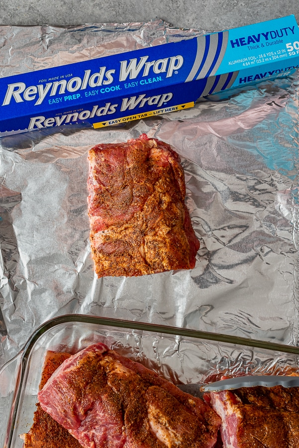 Rack of ribs resting on a sheet of foil to be wrapped and grilled.