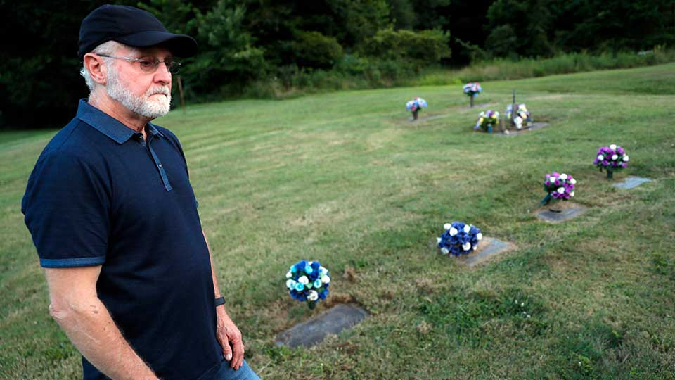 Eddie Davis stands beside the gravestone of his son Jeremy, furthest left, who died from the abuse of opioids, Wednesday, July 17, 2019, in Coalton, Ohio. Members of his family are buried in adjacent plots, including his parents and a sibling.