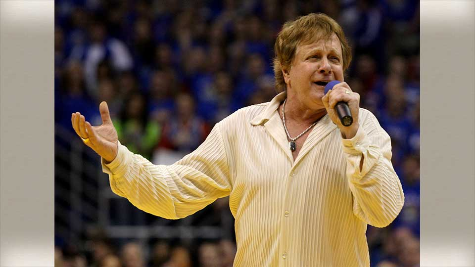 """FILE - In this Jan. 25, 2010 file photo, Eddie Money sings the national anthem before an NCAA college basketball game between Kansas and Missouri in Lawrence, Kan. Eddie Money says he has stage 4 esophageal cancer. The singer known for such hits as """"Two Tickets to Paradise"""" and """"Take Me Home Tonight"""" says his fate is in """"God's hands."""" Money's comments appear in a video released Saturday, Aug. 24, 2019 from his AXS TV reality series """"Real Money."""" The full episode airs Sept. 12.(AP Photo/Charlie Riedel, File)"""