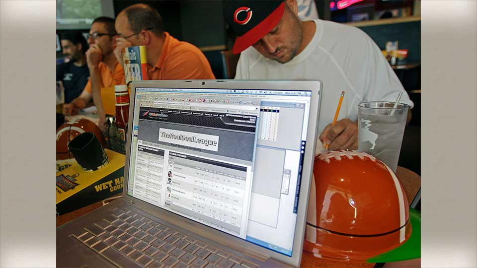 In this Aug. 30, 2010 photograph, Chris Baker, right, checks on players for his mock draft in the Real Deal League for fantasy football players, at a Buffalo Wild Wings restaurant in Cincinnati. Some restaurant chains around the country have launched promotional drives to score with dedicated players of the growing pastime.