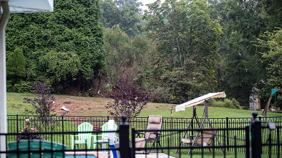Debris from a small plane crash sets in backyards of a residential neighborhood in Upper Moreland, Pa., Thursday, Aug. 8, 2019. Upper Moreland Police Chief Michael Murphy says the plane hit several trees before it finally came to rest. He said everyone aboard the plane was killed.