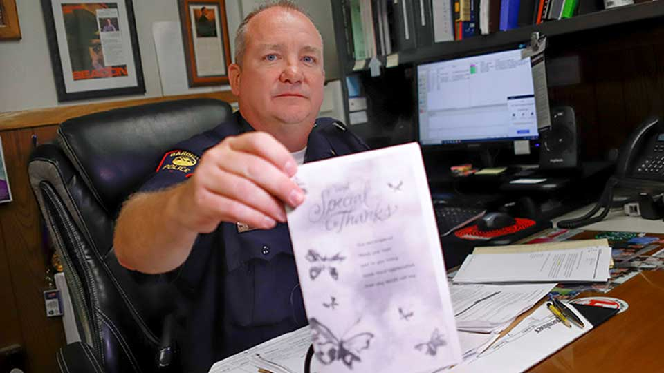 In this Sept. 11, 2019, photo, Barberton Police Chief Vincent Morber shows a copy of a thank-you card that was sent to the department in Barberton, Ohio, for saving the life of the sender, who had overdosed on opioids.