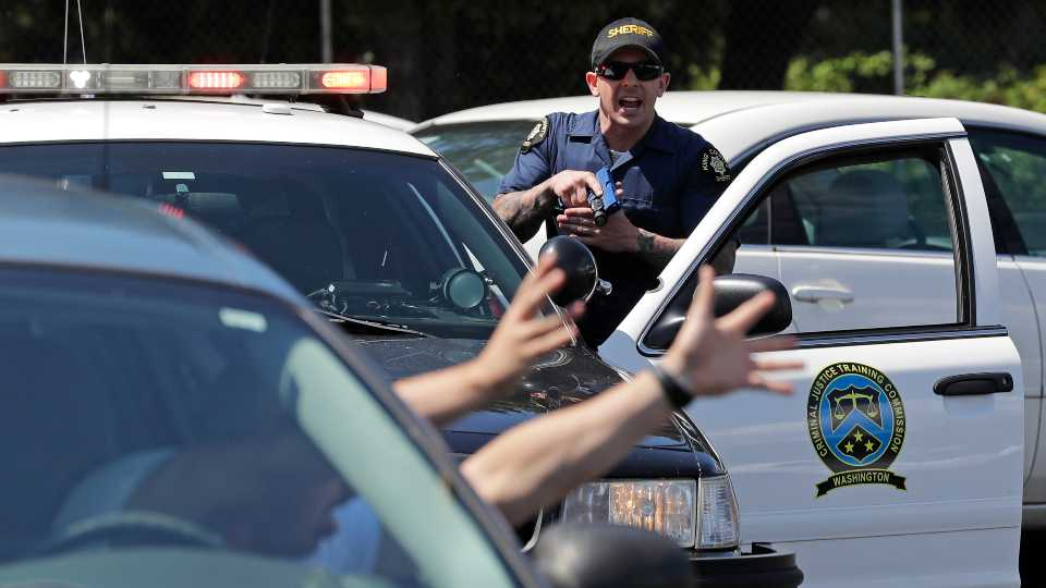 In this July 16, 2019, photo, a King County Sheriff's deputy holds a training weapon as he practices a traffic stop during a class at Washington state's Basic Law Enforcement Academy in Burien, Wash. Accidental shootings by police happen across the United States every year, an Associated Press investigation has found, and cadets at Washington's academy, which is required for all entry-level Washington state law enforcement officers, must have 90 hours of firearms training, but requirements in other states vary widely.