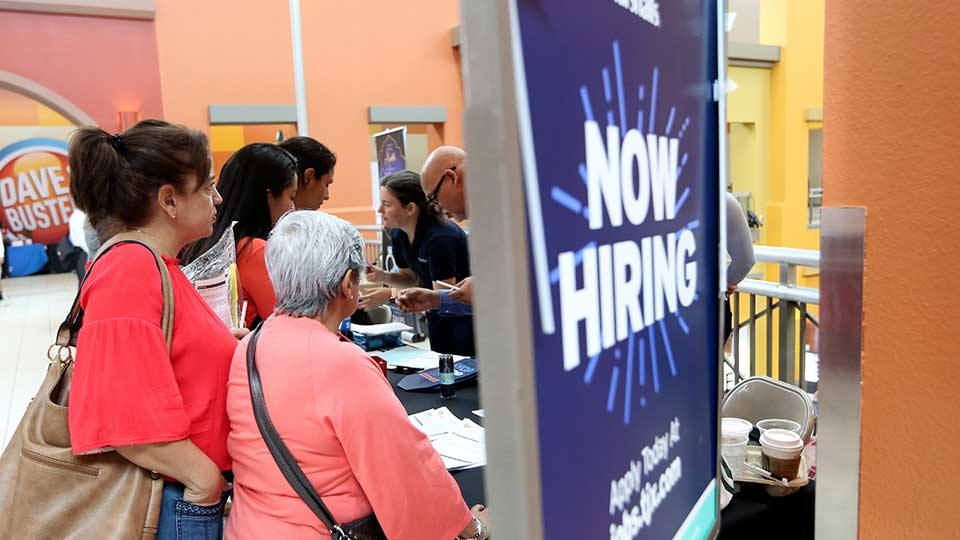 FILE - In this Oct. 1, 2019, file photo people wait in line to inquire about job openings with Marshalls during a job fair at Dolphin Mall in Miami. On Friday, Dec. 6, the U.S. government issues the November jobs report.