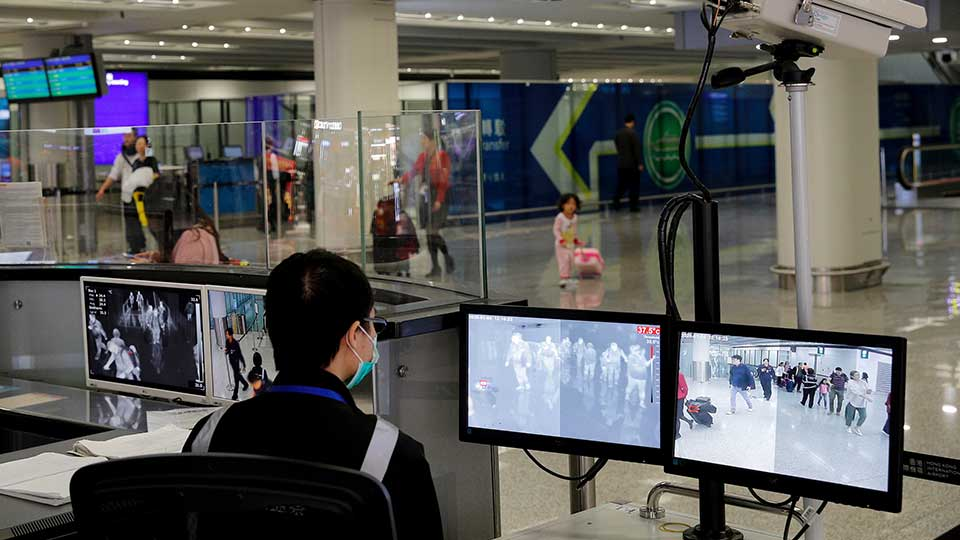 FILE - In this Jan. 4, 2020, file photo, a health surveillance officer monitors passengers arriving at the Hong Kong International airport in Hong Kong. On Friday, Jan. 17, 2020, the U.S. Centers for Disease Control and Prevention officials said they will begin screening airline passengers at three U.S. airports who traveled from Wuhan in central China, for a new illness that has prompted worries about a new international outbreak.
