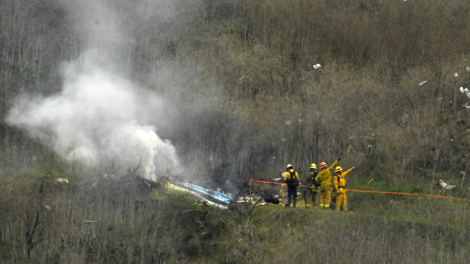 Firefighters work the scene of a helicopter crash Sunday, Jan. 26