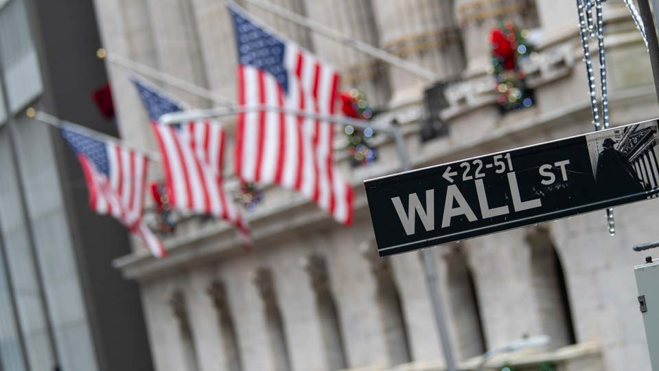 the Wall St. street sign is framed by American flags flying outside the New York Stock Exchange