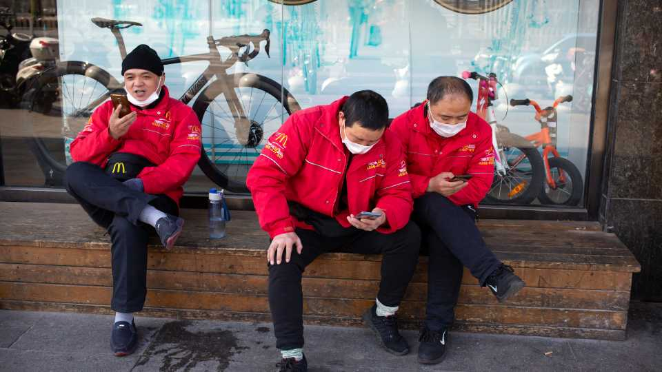McDonald's deliverymen wear face masks as they wait for orders outside a restaurant in Beijing, Saturday, March 7, 2020. Crossing more borders, the new coronavirus hit a milestone, infecting more than 100,000 people worldwide as it wove itself deeper into the daily lives of millions, infecting the powerful, the unprotected poor and vast masses in between.