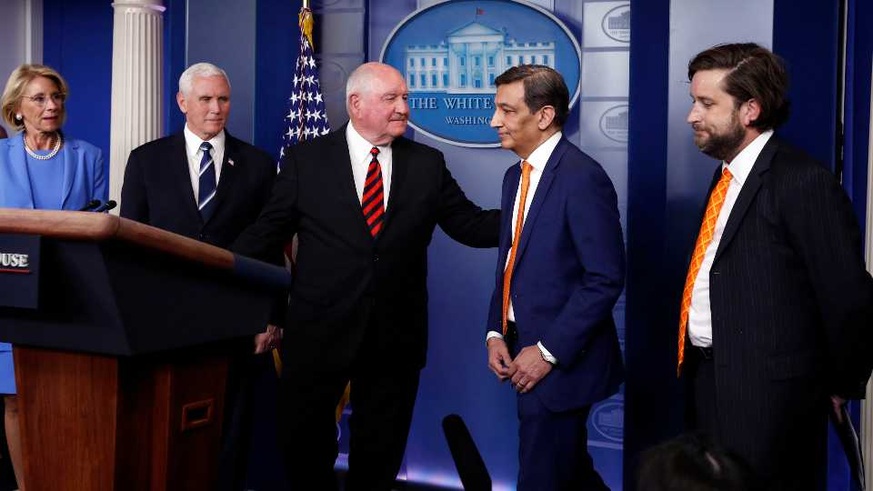 Agriculture Secretary Sonny Perdue invites Panera Bread CEO Niren Chaudhary to speak about the coronavirus response in the James Brady Press Briefing Room, Friday, March 27, 2020, in Washington, as Education Secretary Betsy DeVos, Vice President Mike Pence and McLane Global Logistics chairman Denton McLane watch.