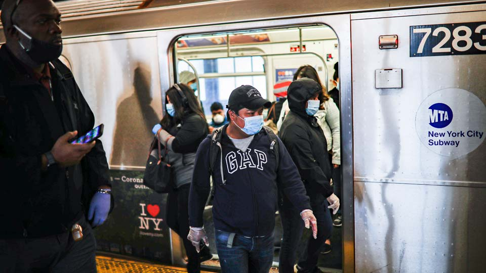 Subway riders, wearing personal protective equipment due to COVID-19 concerns, step off a train