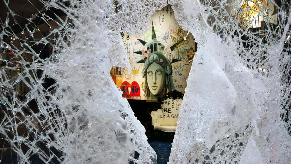 A Statue of Liberty painting is seen through a smashed Dolce and Gabbana store window