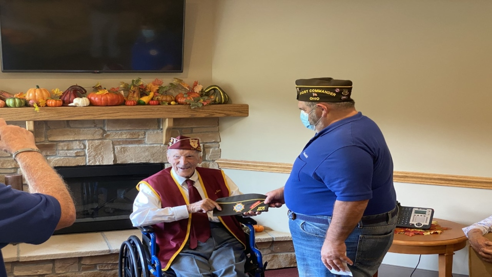 Dominic DiLoreto presents Dan King with a cap as an honorary member of VFM 9571 Ellsworth at Antonine Village Assisted Living.